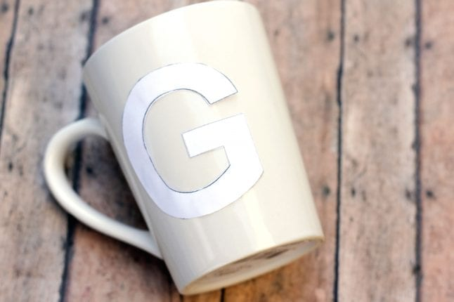 Attach the stencil to you DIY coffee mug with glue dots.