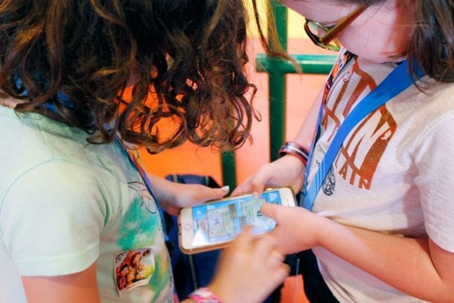 Sisters playing the PLAY Disney Parks app while waiting in line.