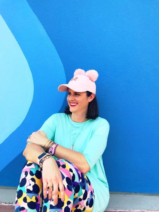 Sarah sitting in front of the popular Blueberry Wall at Epcot with a blue shirt, colorful leggings, and a pink Minnie hat.