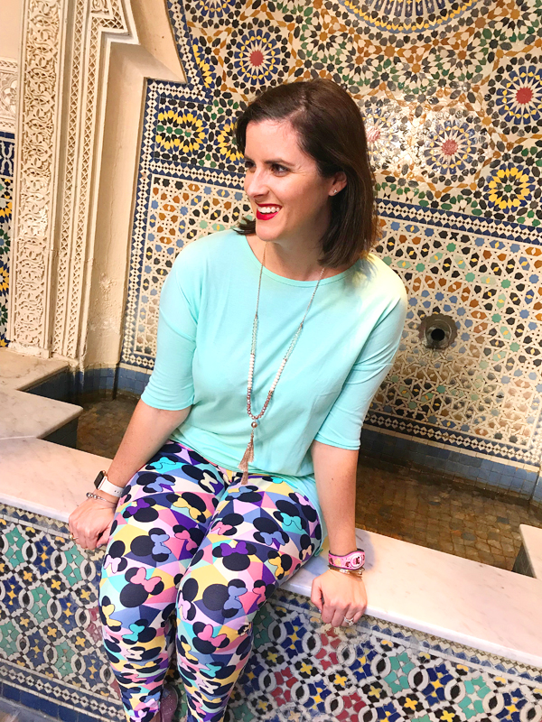 Sarah sitting in front of the Morocco Fountain wall in a blue shirt and colorful leggings.