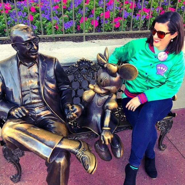Sitting with the Roy and Minnie statue in Magic Kingdom.