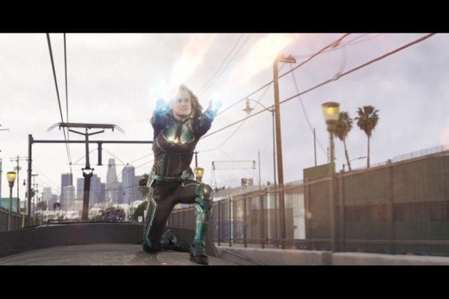 Captain Marvel shooting photon blasts at a Skrull.