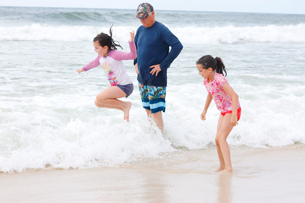 Two girls splashing in the beach at Gulf State Park while their grandpa looks on.