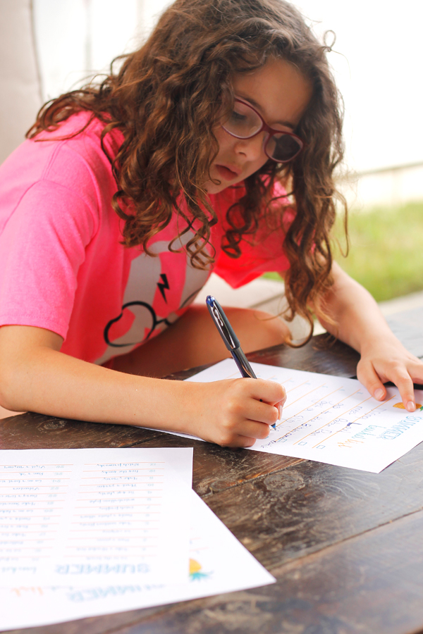 Young girl with curly hair writing our her summer bucket list of activities.