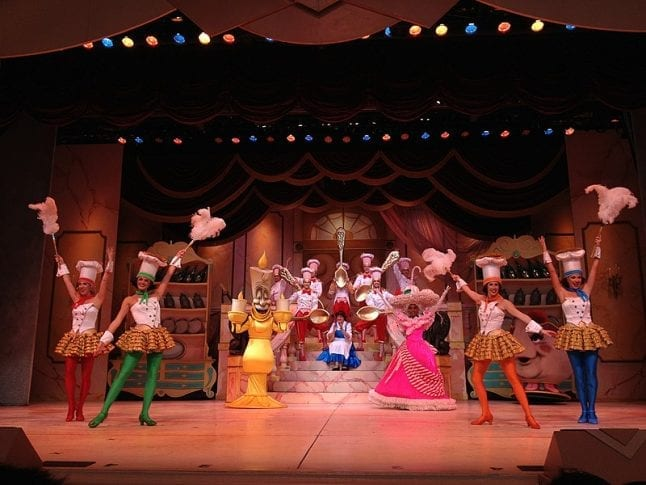 Scene from the Beauty and the Beast stage show featuring Belle and the dishes.