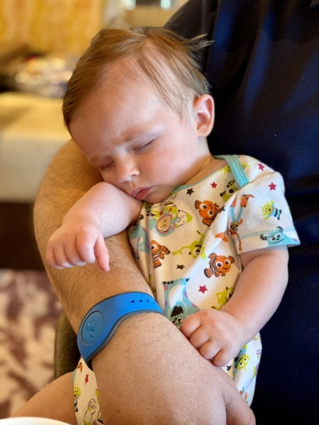 A baby sleeps in his father's arms at meal time.