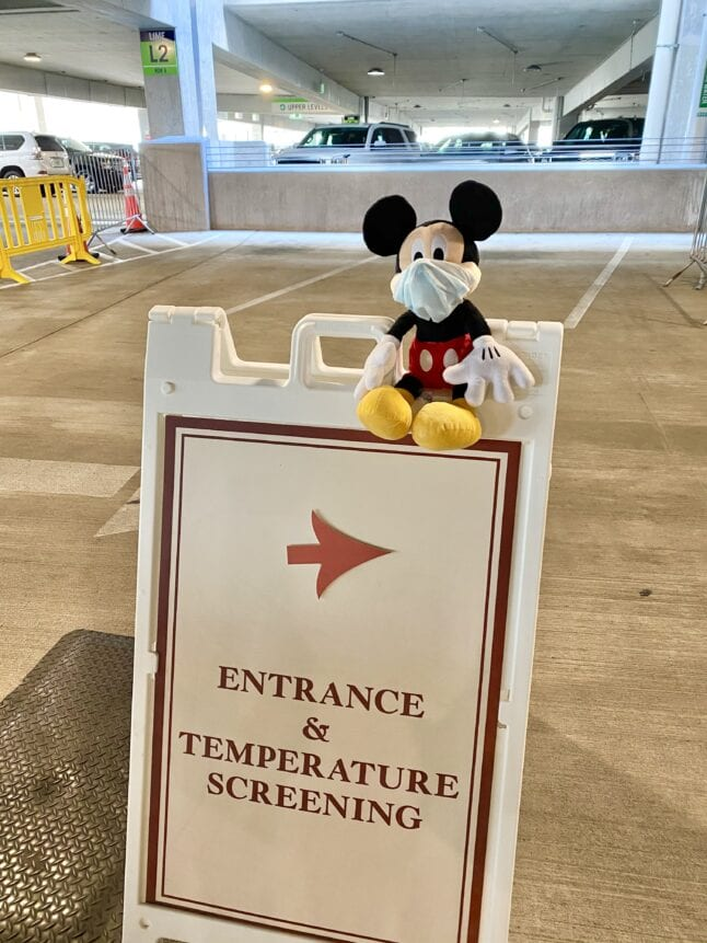 Healthy and safety sign at Disney World with Mickey plush wearing a mask.