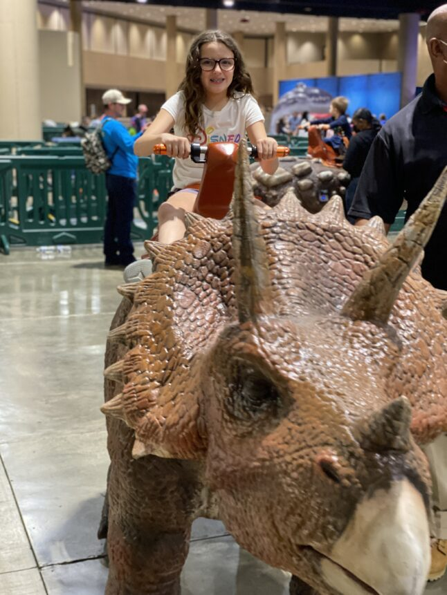 Kids can ride on animatronic dinosaurs at Jurassic Quest.